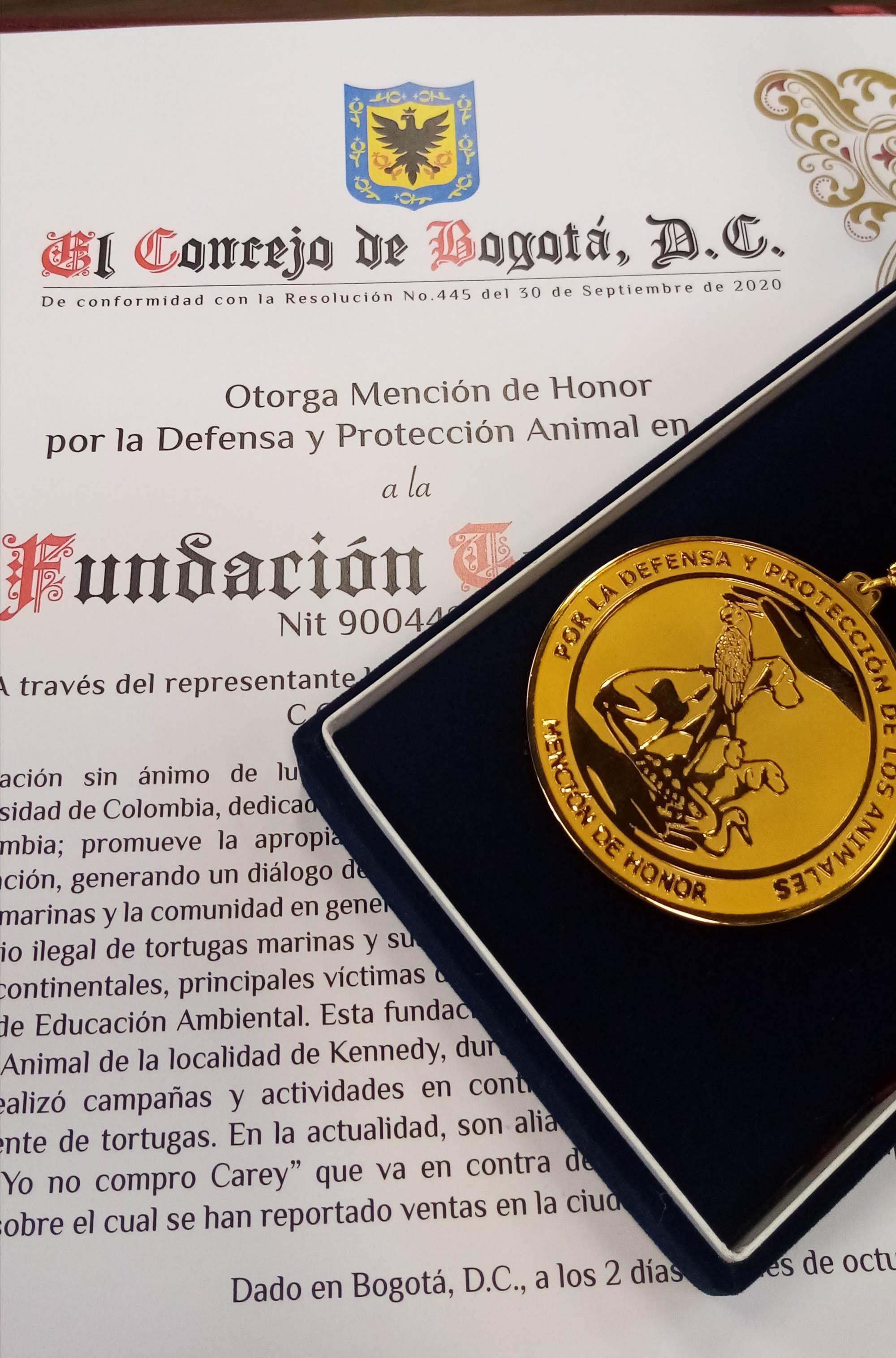 Foto de la mención de honor y medalla otortgada por el concejo de Bogotá. La medalla es dorada con un diseño en el centro de varios animales en medio de dos manos, una arriba y otra abajo. La cinta de la medalla es amarilla y roja, como los colores de la bandera de Bogotá.