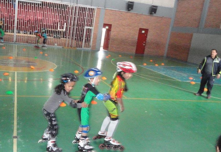 Dos niños ciegos patinando cogidos por la espalda de su guía patinador en un coliseo. Al fondo su entrenador.